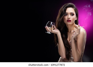 Beautiful glamorous brunette girl wearing a sparkling dress sensually holds in her hands a glass of whiskey with ice and a cigarette smoking smoke. Shimmering makeup, red lips. Black-purple background