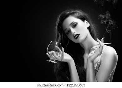 Beautiful glamorous brunette girl wearing a sparkling dress sensually holds in her hands a glass of whiskey with ice and a cigarette smoking smoke. Shimmering makeup. Black and white art style photo
