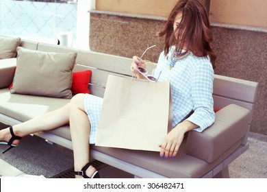 Beautiful glamorous girl in a dress with a paper sack. Rest after shopping. Luxury girl in a checkered dress. Space for text. Girl with sunglasses. Fashion & Style. Stylish Girl.