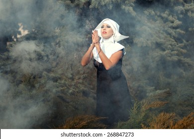 Beautiful glamorous nun folded her arms across her chest, she among the smoke outdoors.