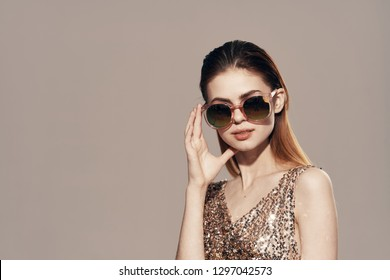 Beautiful glamorous woman in dark round glasses and in a golden dress on a gray background