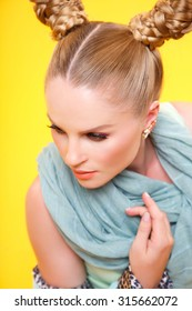 Beautiful glamour blonde woman with fashion make-up and hair-style. closeup portrait on yellow background