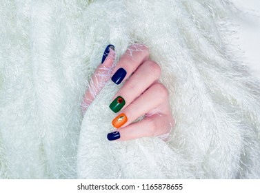 beautiful glamour dark color green blue orange gel nail art decorated with red rhinestone gold metallic on woman fingernails isolated on white soft flesh fur background
