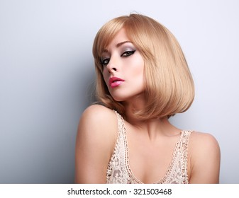 Beautiful glamour makeup blond woman with short hair style posing sexy on blue background