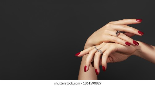 Beautiful glamour photo of elegant female hands with bright burgundy manicure on gray background. Long square nails with dark red gel polish. Luxury fashion style of brilliants jewelry rings