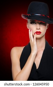Beautiful glamour woman with bright sexy red lips dressed in black dress. Art background.