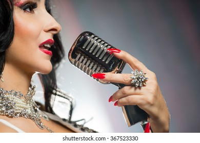 Beautiful glamour woman singing a song with retro microphone.