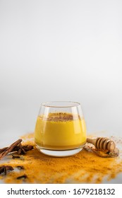 Beautiful glass with golden milk, honey, cinnamon and other ingredients on a white background. Healthy drink. Strengthening immunity. Antioxidant and superfood. Copy space