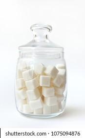Beautiful glass jar with lump sugar on white background.