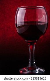 the beautiful glass of red wine was photographed on a red-black background