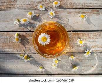 Beautiful glass teacup with chamomile tea on a wooden table among blooming daisies in the rays of the setting sun in Greece