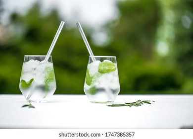 Beautiful glass of water or mojito with lime and mint cocktail on the gree background and white table summer vibe and atmosphere
