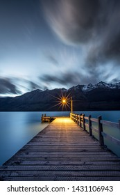 Beautiful Glenorchy pier at sunset, Lake Wakatipu near Queenstown in New Zealand, light at the end, dark cloud moving, mountain background, long exposure landscape.