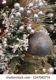 Beautiful glittering christmas ball hanging on xmas tree with silver berries and glowing lights.