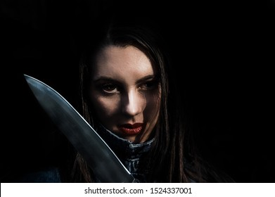 Beautiful gloomy  brunette  girl with a big scary shiny knife. Serial killer and murderer at black background.  Crazy dark  demonic woman as halloween look.