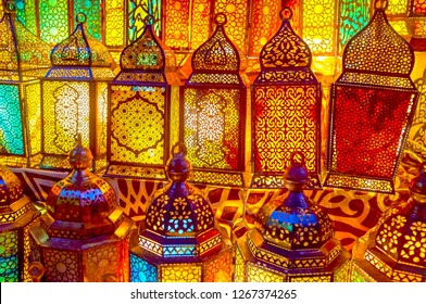The beautiful glowing handmade arabian lamps with different carved metal tracery and colored glass on sale in popular lighting store in Khan El-Khalili market in Cairo, Egypt