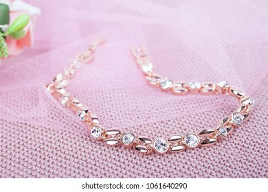 Beautiful gold bracelet on a pink background