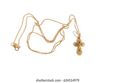 A beautiful gold cross hangs from a chain. Fine jewelry necklace, on white background with shadow