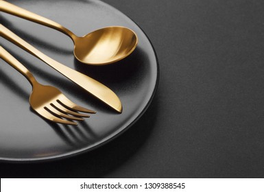 Beautiful gold cutlery - fork, knife, spoon on black plate on black background. Closeup. Horizontal.