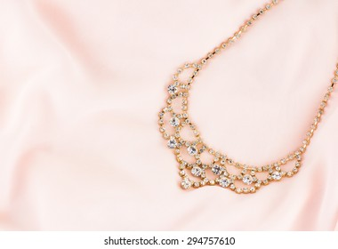 Beautiful gold and diamond necklace on pink background