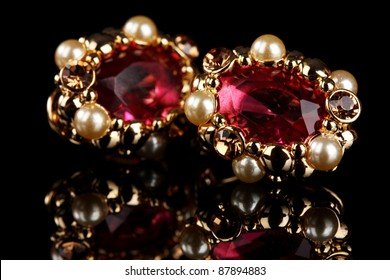 beautiful gold earrings with rubies and pearls on black background