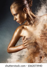 Beautiful gold girl. Fashion woman with golden makeup and bodyart. Fog in the background. Studio shot