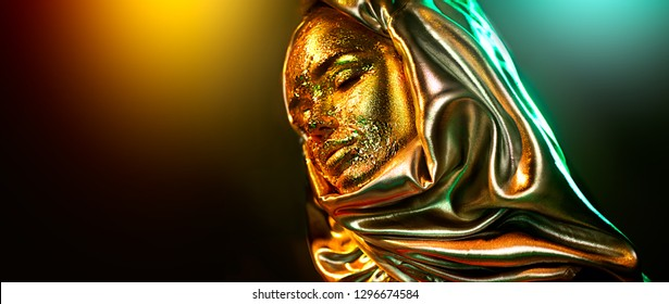 Beautiful gold makeup model girl face portrait. Close up of beauty woman with glamour golden foil makeup isolated on black background in colorful lights. Arabian Muslim dress, hijab, burka, niqab