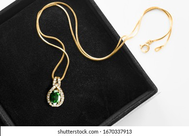 Beautiful gold necklace with emerald and diamonds in jewel box closeup