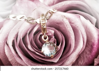 Beautiful gold pendant with big blue topaz and diamonds on rose petals