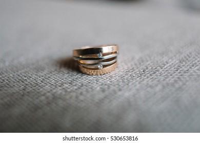 beautiful gold wedding rings with diamonds lying on gray fabric