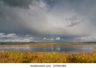 Beautiful Golden autumn views of the tranquil river, Russia, Siberia. Textured cloudy sky.