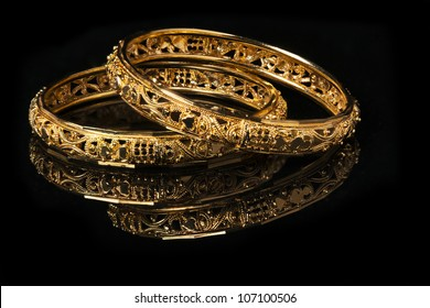 Beautiful golden bangles isolated on black background