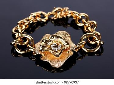 Beautiful golden bracelet with precious stones on grey background