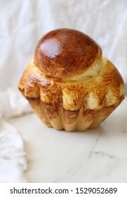 Beautiful golden brown French brioche bread:  'Brioche a tete' , in a brioche mold, against white background. Copy space. French cuisine, pastry, Homemade baking concept.