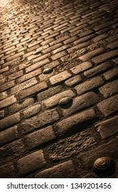 Beautiful golden cobblestone path illuminated by street lights