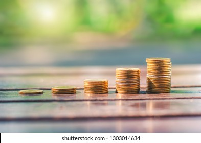 beautiful golden coins stack on wood table with blur nature bokeh background in park with sunrise financial saving banking
