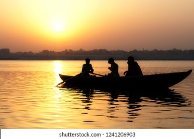 Beautiful Golden dawn on the river. Three people in a boat in the rays of the rising sun