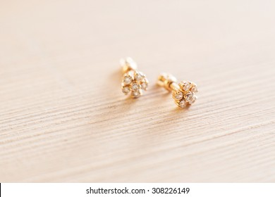 Beautiful golden earring studs with fianit macro shoot on a wooden background