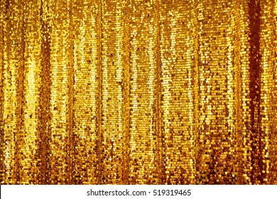 Beautiful golden glitter background. Empty Texture. Holiday background with golden sequins, copyspace, hanging curtain. Sparkling sequined textile