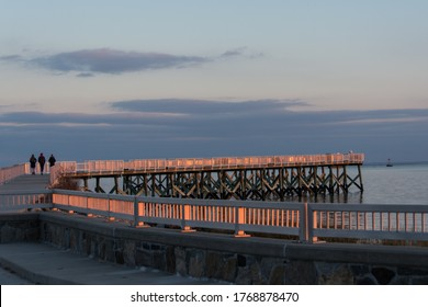 Beautiful golden hour light on the long pier and the Long Island Sound at Calf Pasture Beach in Norwalk, Connecticut USA