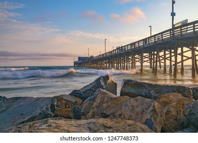 Beautiful golden hour long exposure with colorful scattered clouds as the sun sets over Balboa Pier on Newport Beach in California USA near Anaheim