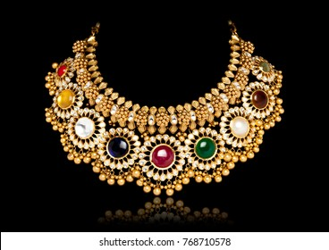 A beautiful golden necklace with multi colored gem stones on dark black background.