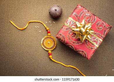 Beautiful golden Rakhi and a wrapped gift box shot from above. 'Raksha Bandhan' festival  is celebrated in India to express love and bond between brother and sister.