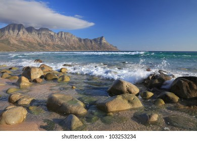 Beautiful golden rocky beach with turquoise water and distant mountains