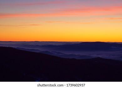 Beautiful golden sky after sunset seen from Sereak mountain in Czech Republic