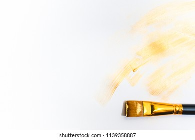 Beautiful golden strokes and a brush isolated on white background.