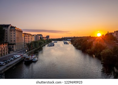 Beautiful golden summer sunset in Stockholm sweden. Perspective of water canal with boats and buildings on the side.