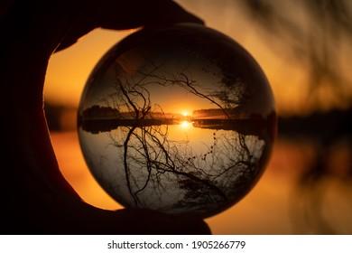 A beautiful golden sunrise over a lake as seen through a lensball.