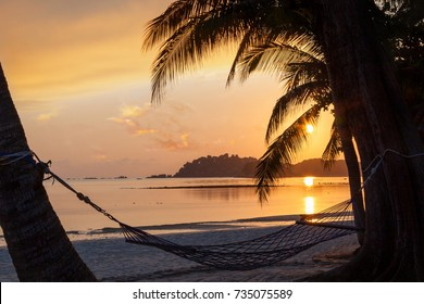 Beautiful golden sunrise over sandy beach on Bintan Island in Indonesia with silhouette of hammock and coconut palm trees with copy space.
