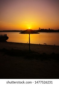 Beautiful golden sunset on a bank shore beach, with umbrella covering the sun, landscape